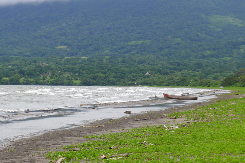 Nicaraguan beach with small boat and green mountain