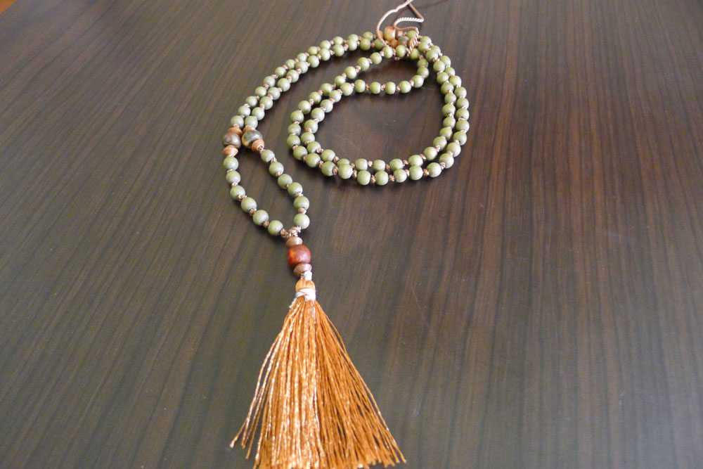 A traditional mala with 108 wooden beads + buddah bead + tassle